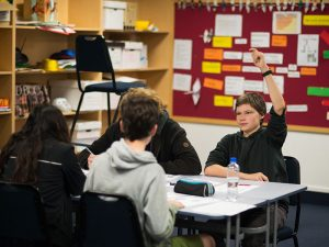 Student with hands up in Geography class