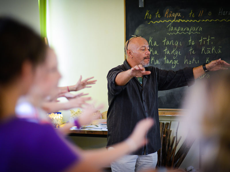 Teacher showing kapa haka in Maori class