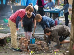 Students lighting up camp fire outdoor
